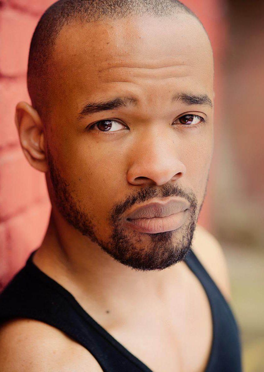 black male actor in vest